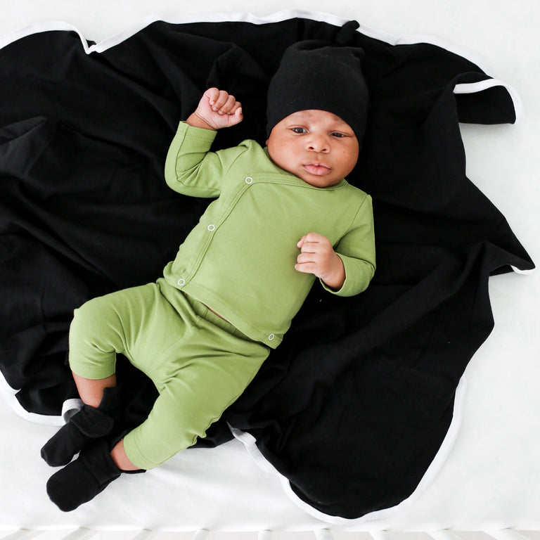 BABY SHOWN WEARING THE ONYX FRESH BABY KNOTTED HAT, LAYING ON AN ONYX BLANKET AND WEARING A GREEN COMING HOME OUTFIT AND ONYX BOOTIES, BABY IS LOOKING INTO THE CAMERA