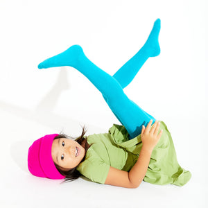CHILD LAYING ON BACK WEARING TIGHTS WITH LEGS KICKING IN THE AIR
