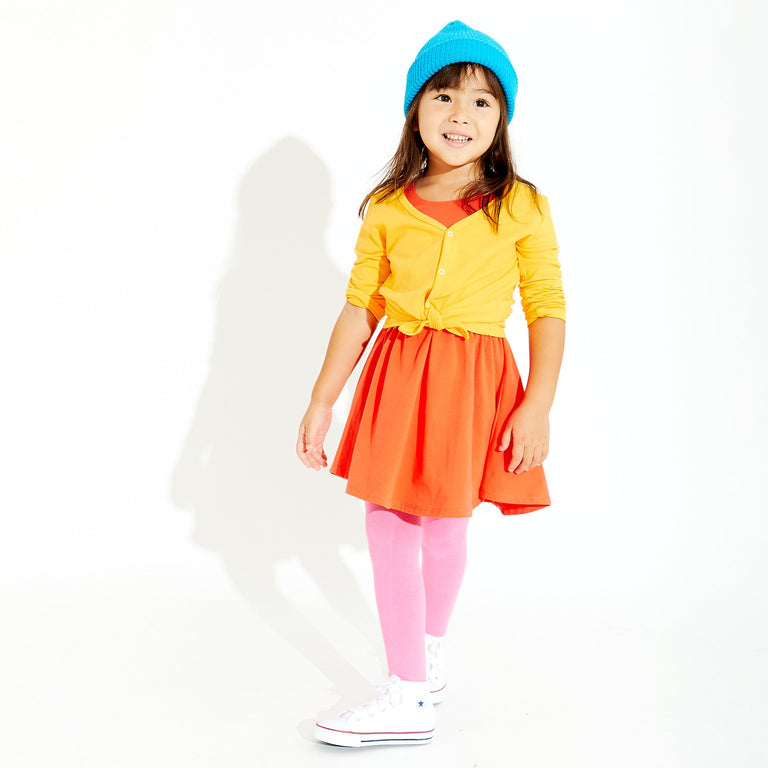 BUBBLEGUM TIGHTS WORN BY CHILD IN DRESS AND CARDIGAN