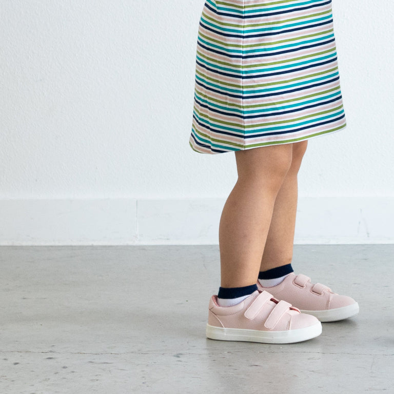 NAVY SHORT SOCK STRIPE SET SHOWN ON CHILD STANDING, PAIRED WITH LIGHT PINK SHOES AND OUR RETRO STRIPE HI-LO DRESS