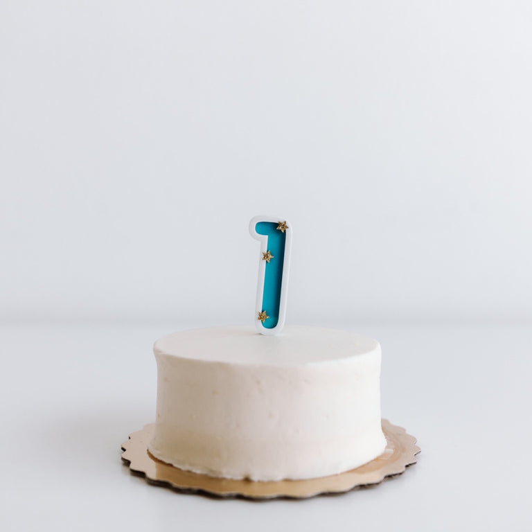 Eleanor Moss Number Cake Topper 1 // Teal Photo of topper on a small cake against a white wall