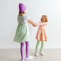 Thumbnail for violet and pistachio tights shown on children holding hands and spinning.