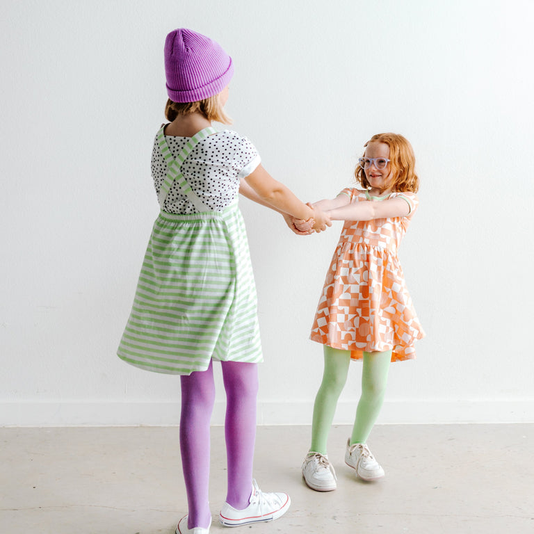 VIOLET AND PISTACHIO TIGHTS SHOWN ON CHILDREN HOLDING HANDS AND SPINNING.