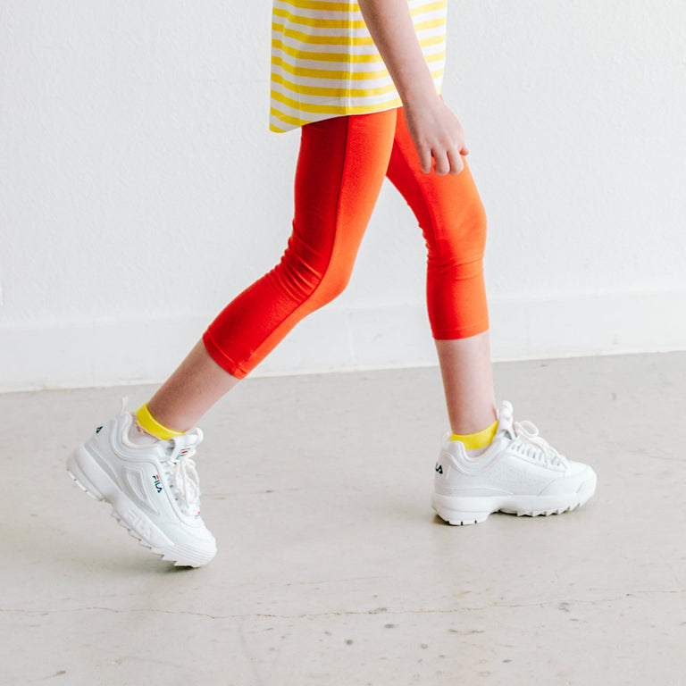 LEMON STRIPE SHORT SOCKS SHOWN ON CHILD PAIRED WITH RED PANTS AND WHITE SHOES
