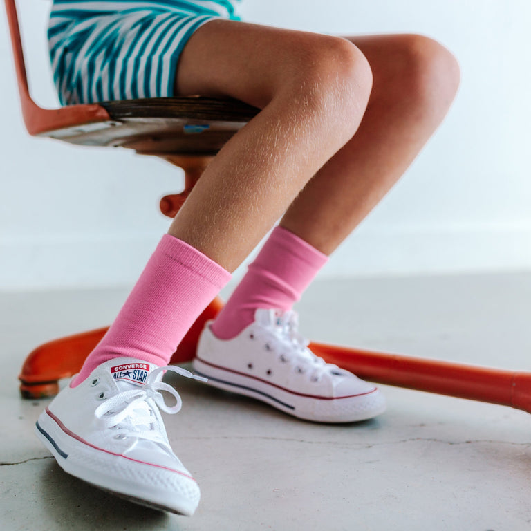 BUBBLEGUM SOLID TALL SOCK SHOWN ON CHILD SITTING AT A DESK PAIRED WITH WHITE SHOES