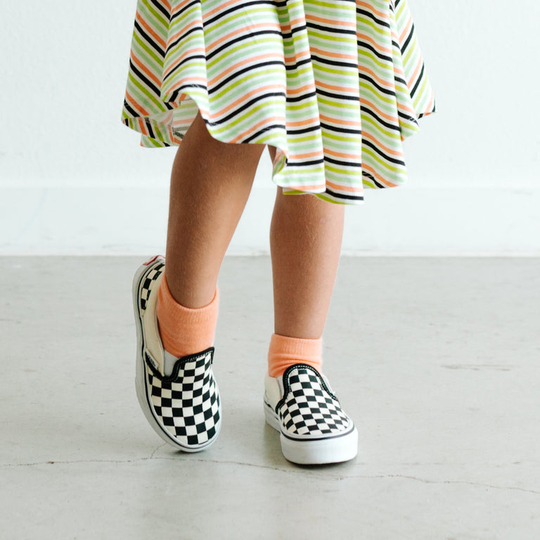 GRAPEFRUIT SOLID SHORT SOCK SHOWN ON CHILD PAIRED WITH STRIPE DRESS AND CHECKERED SHOES