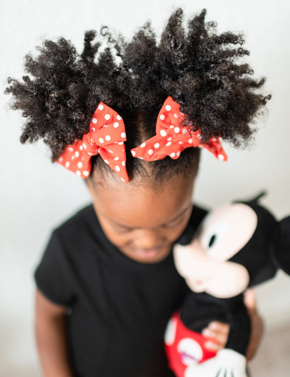 POPPY WITH SNOW DOT EVERYDAY BOWS SHOWN ON CHILD HOLDING MICKEY MOUSE PLUSH
