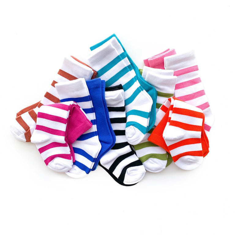 FULL LINE UP OF TALL SOCKS PILED TOGETHER ON A WHITE BACKGROUND