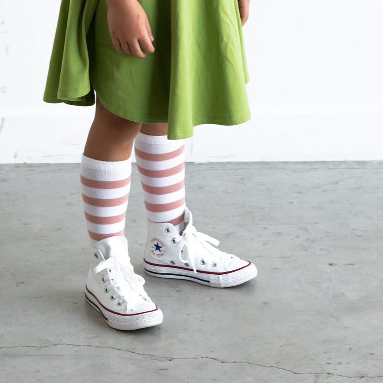 ROSE KNEE HIGH, STRIPES SHOWN ON CHILD PAIRED WITH TENNIS SHOES AND GREEN DRESS