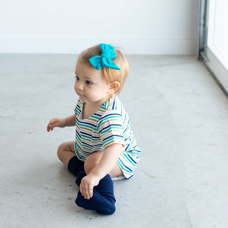 PEACOCK EVERYDAY BOW SHOWN ON TODDLER SITTING ON THE FLOOR LOOKING OFF TO THE SIDE
