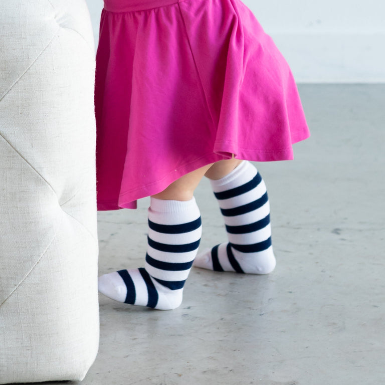NAVY KNEE HIGH, STRIPES SHOWN ON TODDLER UP CLOSE PAIRED WITH A RASPBERRY SWING DRESS