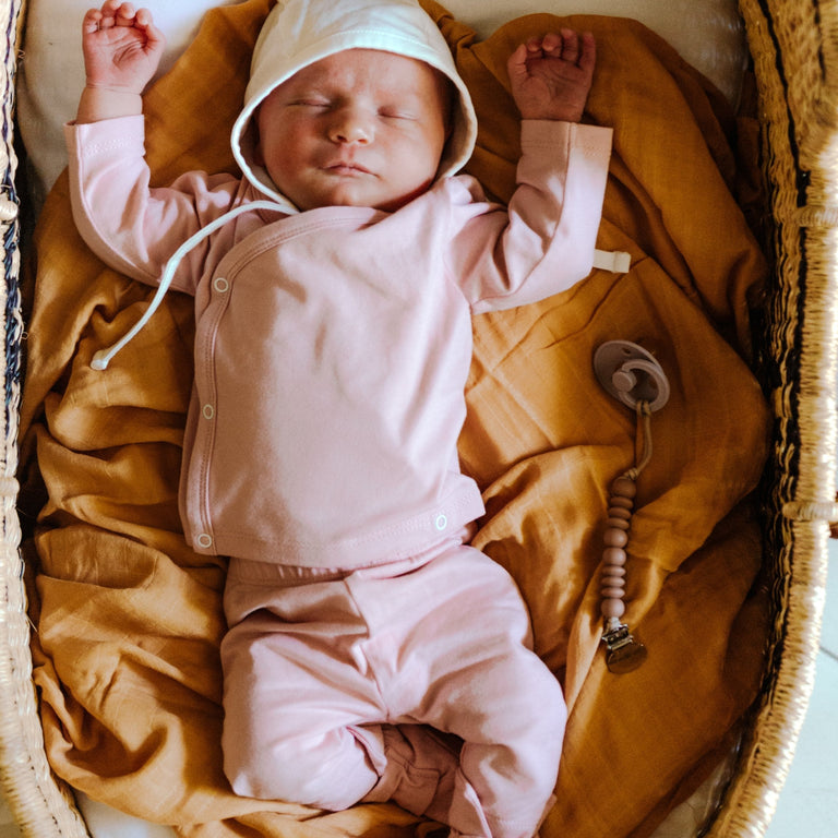 BABY SLEEPING IN BASSINET WITH ARMS UP WITH RUST PRETTY PLEASE TEETHER