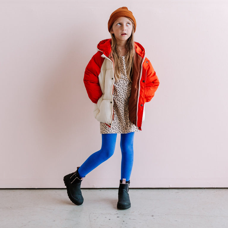 COBALT KNIT TIGHTS SHOWN ON CHILD WEARING A TEE DRESS AND PUFFY COAT STANDING IN FRONT OF A WALL LOOKING UP.