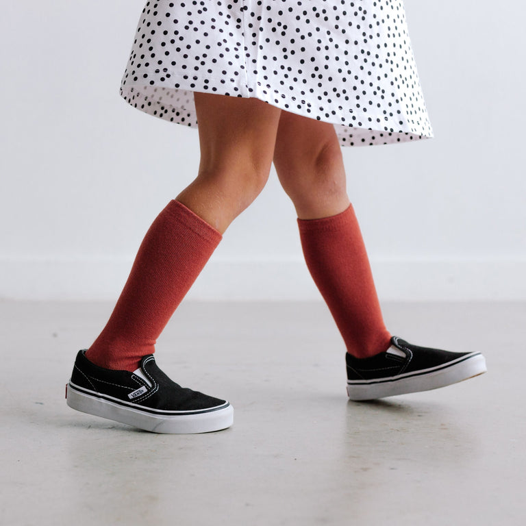 RUST TALL SOCKS SHOWN ON CHILD WALKING IN A DRESS AND SNEAKERS