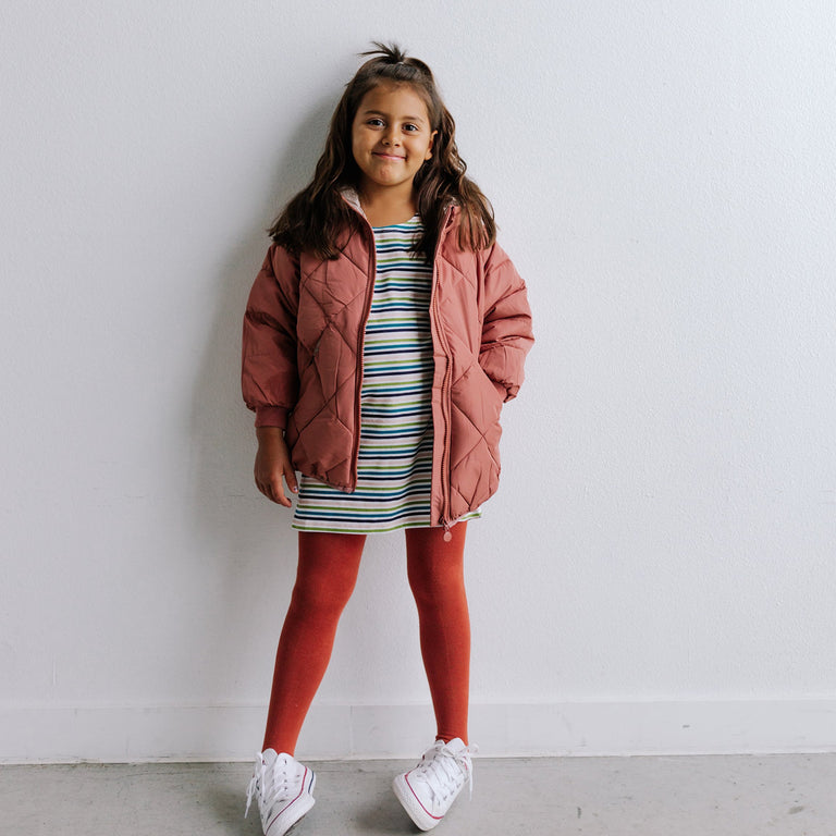 RUST TIGHTS SHOWN ON CHILD WITH DRESS AND PUFFY COAT