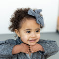 Thumbnail for charcoal everyday bow shown on toddler smiling towards the camera resting her head on her hands