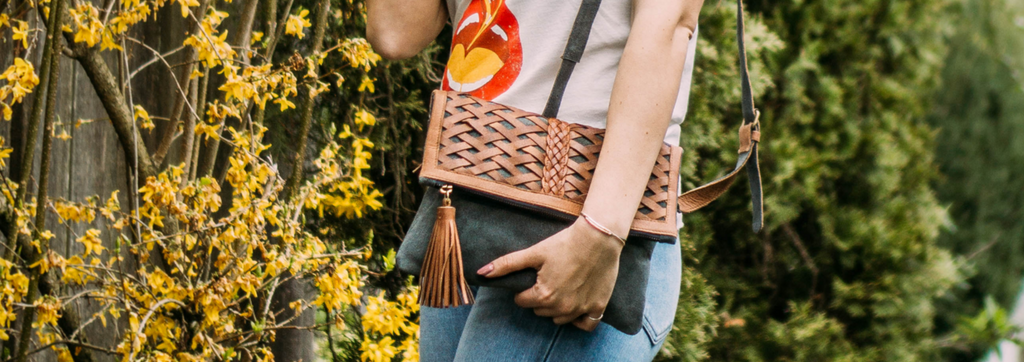 woman outdoors in front of plants in sun wearing a clutch, braided and woven leather, Ivy clutch.