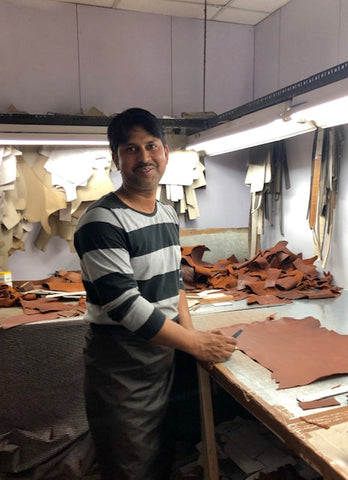 leathercrafter in india, cutting individual pieces of leather.