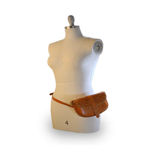 Tooled leather belt bag on mannequin, Cassie Convertible Crossbody Bag.