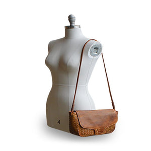 Brown woven leather bag with smooth flap on mannequin, Sawyer Woven Shoulder Bag.