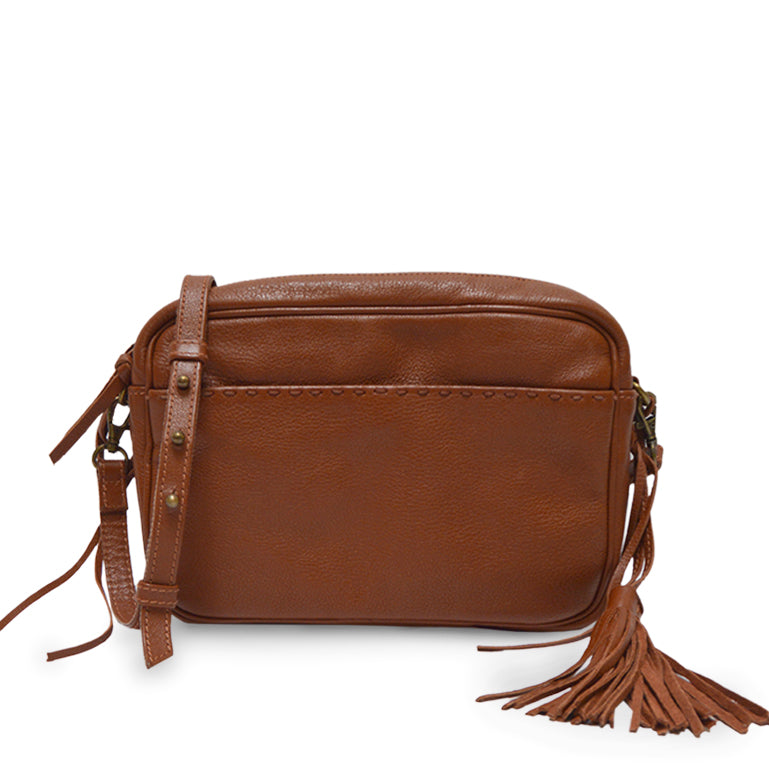 Brown leather shoulder bag in front of a woman, Willow Tassel Shoulder Bag.