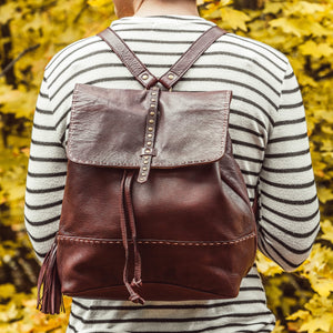 Back of a woman wearing a brown leather backpack in front of fall foliage, Beth Leather Backpack.