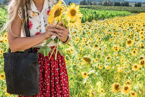 Woman standing in a field of sunflowers with a black leather tote with brushed gold round rings going down the middle panel, Petra Leather Tote.