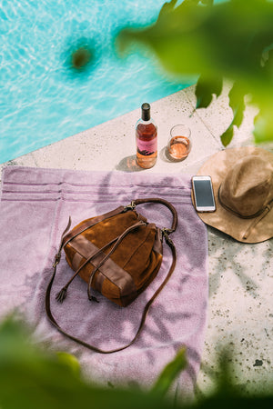 Red brown bucket bag on towel by the pool, Rowan Suede Crossbody Bag.