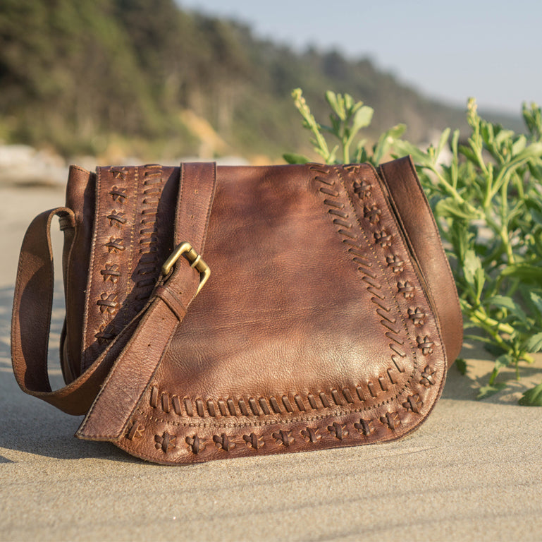 Boho leather saddle bag on the ground next to the beach, Saddle Crossbody Bag.