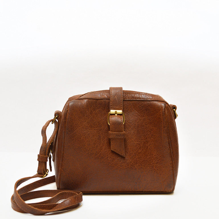 Woman wearing a brown purse by tree, Sam Leather Crossbody Bag.