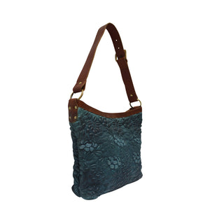 Blue leather shoulder bag at an angle with handle up, quilted floral detail, Cari Quilted Shoulder Bag.