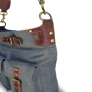 Close up image of the leather trim on the side of the gray-blue canvas crossbody bag, Daily Crossbody Bag.