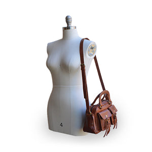 Brown leather bag with two pockets and a handle on a mannequin, Dora Crossbody Bag.
