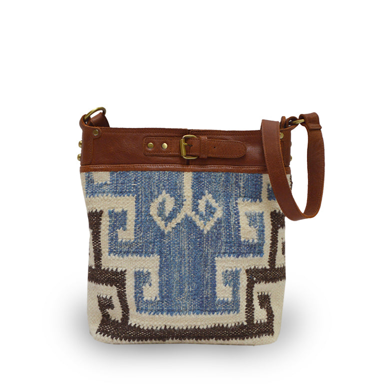 Blue and cream textured crossbody bag, bag is on the ground outside, Elsie Crossbody Bag.