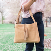 woman outside wearing a braided leather handbag, Grace Shoulder Bag.