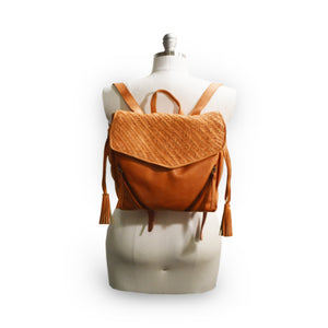 Coral leather backpack with woven flap on mannequin, Julie Leather Backpack.