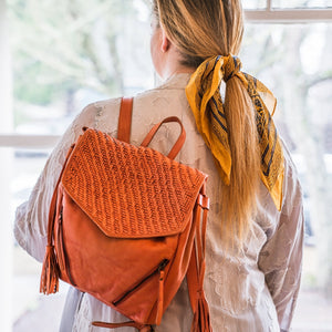 Woman wearing coral leather backpack, Julie Leather Backpack.