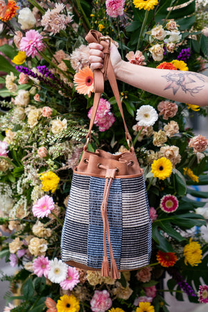 Canvas bucket bag in front of a flower installation in Portland, Madison Bucket Bag.