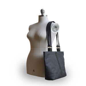 Black leather tote with brushed gold round rings going down the middle panel on a mannequin, Petra Leather Tote.