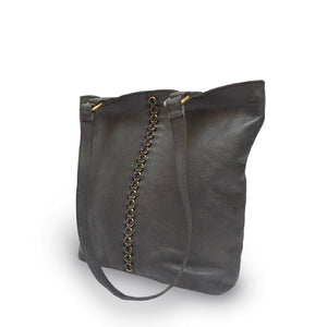 Black leather tote at an angle with brushed gold round rings going down the middle panel, Petra Leather Tote.