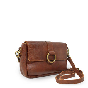 Small leather crossbody bag with a brass ring on the front, bag at an angle, Sabrina Crossbody Bag.