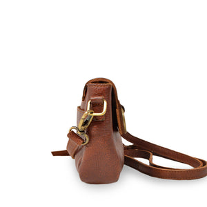 Small leather crossbody bag with a brass ring on the front handle up, side view, Sabrina Crossbody Bag.