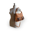 Small caramel crossbody bag with two exterior pockets, on mannequin, Stardust Crossbody Bag.