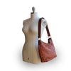 Rust leather shoulder bag on mannequin, quilted floral detail, Cari Quilted Shoulder Bag.