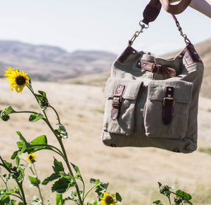 Green canvas bag held in a scenic area with sunflowers, Daily Crossbody. Bag.