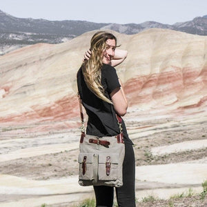 Woman standing in front of the painted hills in Oregon wearing a large unisex canvas crossbody bag, Daily Crossbody Bag.