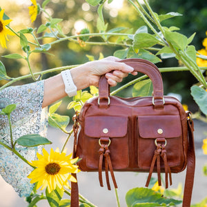 Leather purse being held in front of sunflowers, Dora Crossbody Bag.