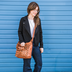 woman outside next to blue wall wearing a leather tote, Haddie Woven Tote.