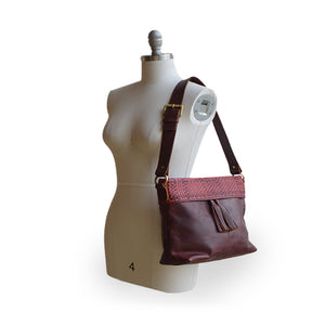 Wine colored leather shoulder bag on a mannequin Nomi Shoulder Bag.