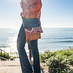 Woman standing in front of the ocean wearing a leather crossbody bag with a fabric flap, Idina Jacquard Clutch.